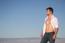hot man with an open shirt outdoors overlooking a mountain range