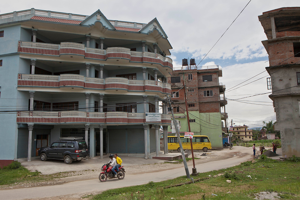 Street scene in Kathmandu, Nepal.  A motorbike passes outside the Hamro Ghar centre which is a temporary care home for young people who have been rescued from illegal labour in carpet factories.