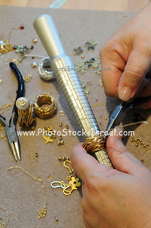 Jeweller forms a ring by winding gold wire on a finger mould