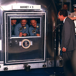 """Pacific Ocean - (FILE) -- United States President Richard M. Nixon was in the central Pacific recovery area to welcome the Apollo 11 astronauts aboard the U.S.S. Hornet, prime recovery ship for the historic Apollo 11 lunar landing mission. Already confined to the Mobile Quarantine Facility (MQF) are (left to right) Neil A. Armstrong, commander; Michael Collins, command module pilot; and Edwin E. Aldrin Jr., lunar module pilot. Apollo 11 splashed down at 11:49 a.m. (CDT), July 24, 1969, about 812 nautical miles southwest of Hawaii and only 12 nautical miles from the U.S.S. Hornet. The three crew men will remain in the MQF until they arrive at the Manned Spacecraft Center's (MSC) Lunar Receiving Laboratory (LRL). While astronauts Armstrong and Aldrin descended in the Lunar Module (LM) """"Eagle"""" to explore the Sea of Tranquility region of the Moon, astronaut Collins remained with the Command and Service Modules (CSM) """"Columbia"""" in lunar-orbit. Handout Photo by NASA via CNP/ABACAPRESS.COM"""