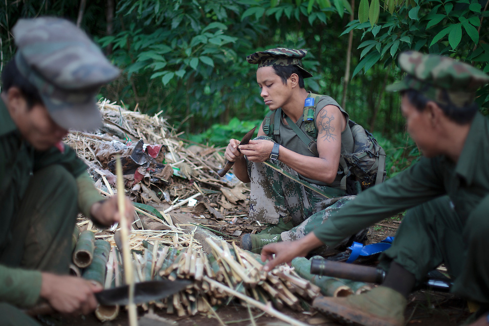 KIA's members sharpen bamboo's sticks for put on the ground of the jungle like traps, in Rubber Hill Post in the frontline, Laja Yang village outskirts of Laiza, Kachin State, Myanmar on August 8, 2012. The KIA formed in 1961 in response to a military coup in Burma led by General Ne Win, who attempted to consolidate Burmese control over regions on the periphery of the state which were home to various ethnic groups. From 1961 until 1994, the KIA fought a grueling and inconclusive war against the Burmese junta. In 2011, general Sumlut Gun Maw confirmed renewed fighting in the state of Kachin for independence. One of the new reasons for the ending of the ceasefire is the creation of the Myitsone Dam which requires the submergence of dozens of villages in Kachin state.