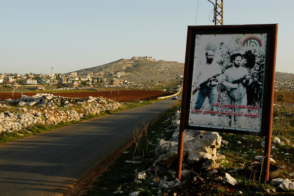 A billboard depicting militants in southern Lebanon near the boarder with Israel. The Beaufort castle, the background was a military outpost during the Israeli occupation of southern Lebanon..Yohmour, Lebanon. 25/11/2008..Photo © J.B. Russell
