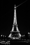The Eiffel Tower shines brightly in Paris night sky.