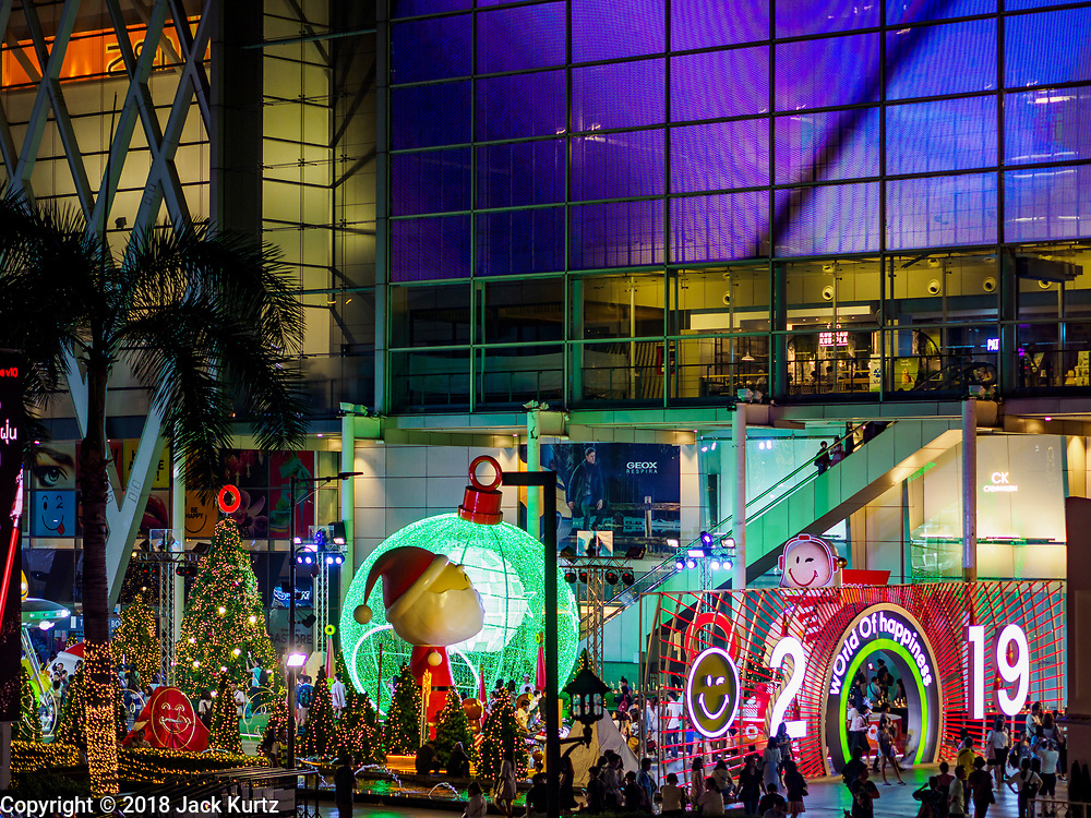"""23 NOVEMBER 2018 - BANGKOK, THAILAND:  People in front of the """"World of Happiness,"""" the Christmas display at Central World, a large mall in Bangkok. Although Thailand is an overwhelmingly Buddhist country, the commercial aspects of Christmas are widely observed, especially in Thailand's urban areas, which have large concentrations of Europeans and Americans.     PHOTO BY JACK KURTZ"""