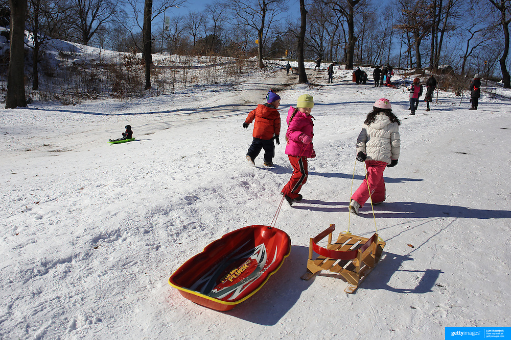 Youngsters pull their sleds back up the hill while sledding in Central Park after New York City was hit with over 7 inches of snow during its first winter storm of the year. Central Park, Manhattan, New York, USA. 4th January 2014 Photo Tim Clayton