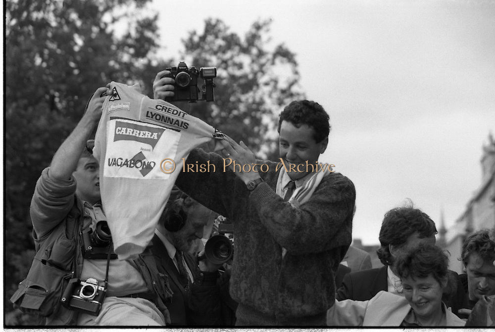 Stephen Roche, Tour de France Winner.  (R61)..1987..26/27 .07.1987..07. 26/27.1987..26/27th July 1987..Tour de France Winner Stephen Roche, the first Irishman to do so , was feted on his arrival back in Dublin. The people of Ireland descended on Dublin to throng the streets as they congratulated Stephen on his momentous achievement...Proudly waving his winner's Yellow Jersey, Stephen Roche is paraded through the streets of Dublin.