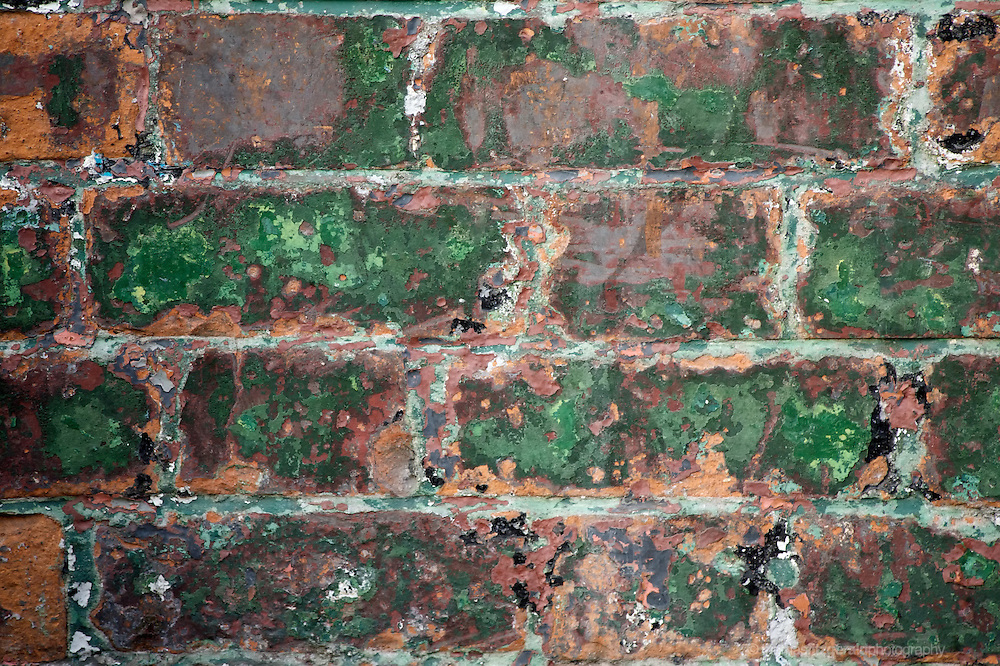 The wonderful patterns of peeled and faded paint over some old red brick block work on this interesting multicolored brick wall.