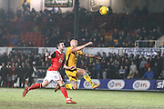 Aaron Wildig of Morecambe FC has an effort on goal under pressure from David Pipe of Newport County during the EFL Sky Bet League 2 match between Newport County and Morecambe at Rodney Parade, Newport, Wales on 21 February 2017. Photo by Andrew Lewis.