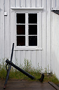 Old house and anchor at the small settlement of Töa at Tindsöya, Vestraalen, Norway.
