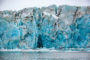 The ice of blue icebergs contains fewer air bubbles than those appearing more or less white. On rainy days their colour appears particularly intense. This big iceberg is floating in Burgerbukta, part of Hornsund, Spitsbergen, Svalbard, Norway.