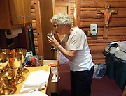 PRICE CHAMBERS / NEWS&amp;GUIDE<br /> Shirley Craighead smells a bottle used for communion in the sacristy, where she cares for items used by the church.