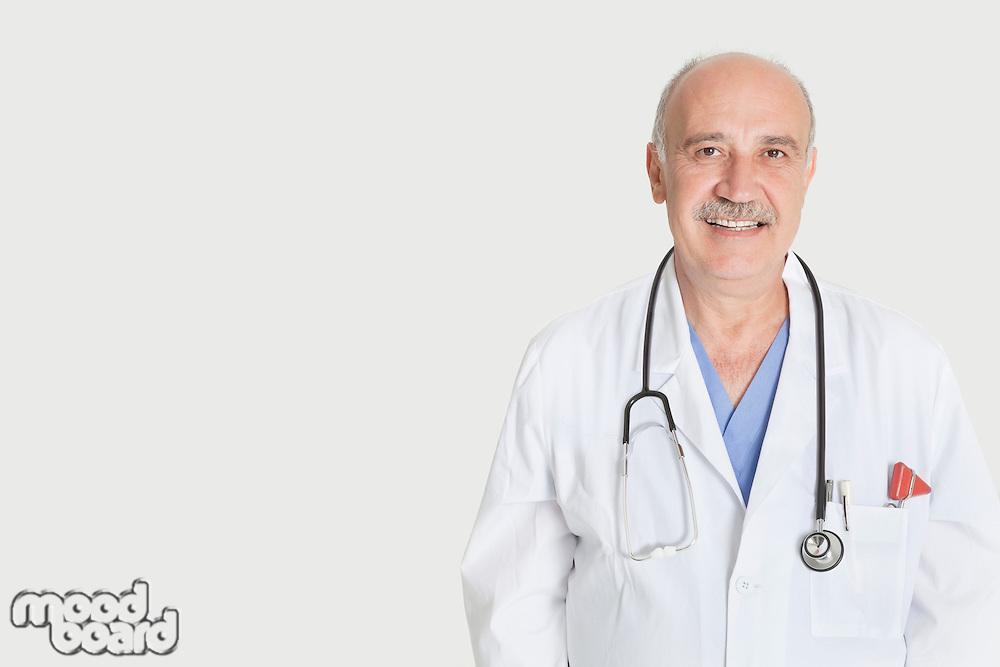 Portrait of happy senior medical practitioner over gray background