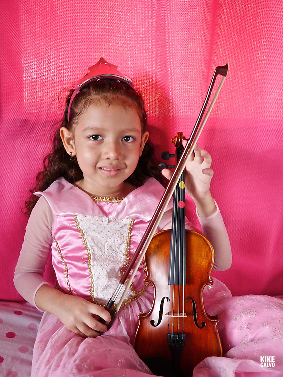Latin girl dressed like a princess playing the violin in a pink room