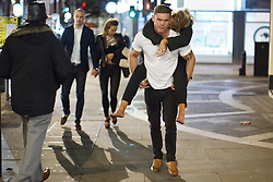 "© licensed to London News Pictures. London, UK 14/12/2013. A ""Mad Friday"" reveller carries his drunk partner in Soho, London whilst enjoying the last Friday night out before Christmas, which is also the busiest night of the year for emergency services. Photo credit: Tolga Akmen/LNP"