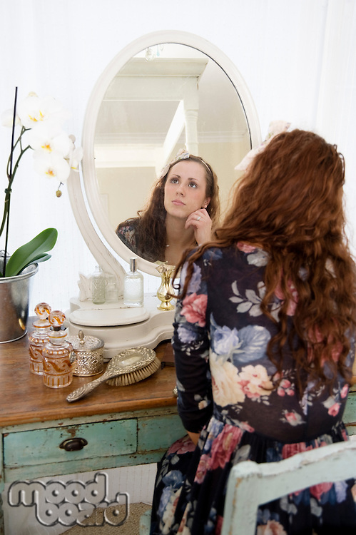 Thoughtful young woman sitting in front of mirror