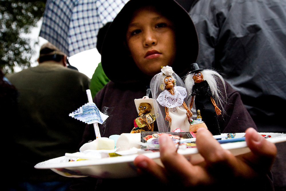 A childs holds a hand made scene of a family representing Sante Muerte in Tipito, Mexico City.