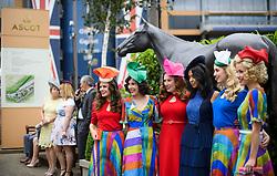 © Licensed to London News Pictures. 19/06/2018. London, UK.  A groups of colourfully dressed racegoers pose for a photograph while attending day one of Royal Ascot at Ascot racecourse in Berkshire, on June 19, 2018. The 5 day showcase event, which is one of the highlights of the racing calendar, has been held at the famous Berkshire course since 1711 and tradition is a hallmark of the meeting. Top hats and tails remain compulsory in parts of the course. Photo credit: Ben Cawthra/LNP
