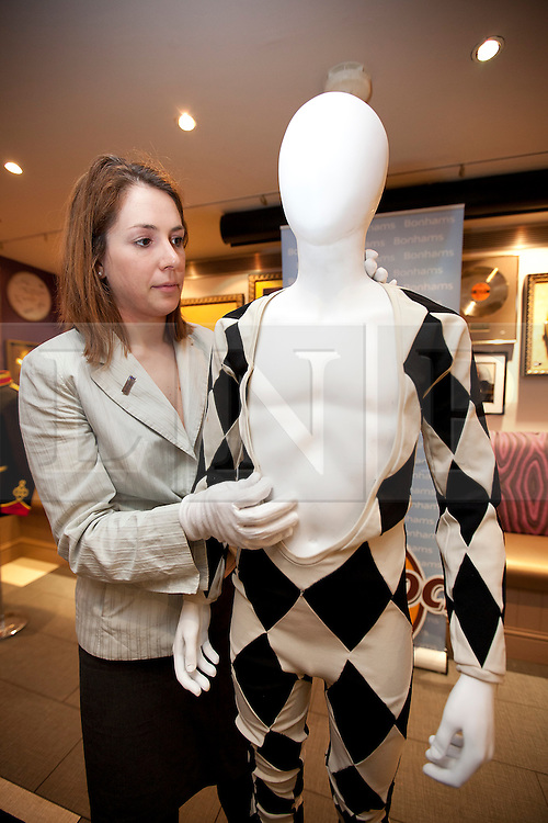 © Licensed to London News Pictures. 27/06/2012. LONDON, UK. A member of Bonhams staff tends to Freddie Murcury's iconic jumpsuit at London's Hard Rock Cafe today (27/06/12). The late singer's suit, and other pieces, were on display at London's Hard Rock Cafe ahead of an auction of entertainment memorabilia being held at Bonhams' Knightsbridge auction house on the 3rd of July. Photo credit: Matt Cetti-Roberts/LNP