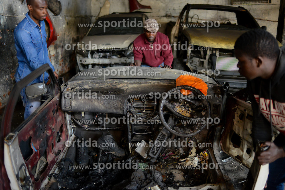 People move a burnt vehicle at a Nigerian-owned garage in Johannesburg Town, South Africa, on April 17, 2015. South African police on Friday fired rubber bullets to disperse rioters in central Johannesburg, a fresh hotbed of xenophobia violence. The current spate of xenophobic violence mainly affects Durban and Johannesburg. According to official figures, five people have been killed and thousands of immigrants displaced. EXPA Pictures © 2015, PhotoCredit: EXPA/ Photoshot/ Zhai Jianlan<br /> <br /> *****ATTENTION - for AUT, SLO, CRO, SRB, BIH, MAZ only*****