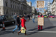 On the occasion of Commonwealth Day, a woman carrying a plastic bag walks past an environmental activist standing in Parliament Square, advocating the ban on plastics around the world, on 11th March 2019, in Westminster, London, England.