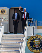 PRESIDENT DONALD J. TRUMP waves as he exits Air Force One with United States Secretary of Housing and Urban Development, BEN CARSON, in Reno, Nevada, on Wednesday, August 23, 2017. Trump is speaking at the American Legion convention at the Reno-Sparks Convention Center. The American Legion is a war time veterans association that often holds its annual convention at the Reno-Sparks Convention Center.