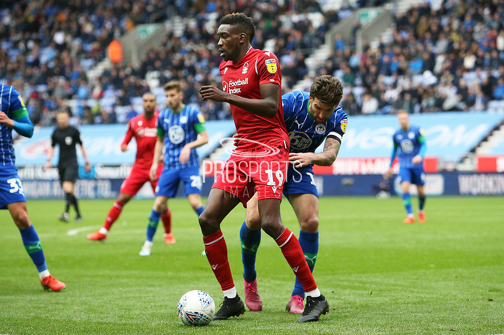 Nottingham Forest forward Sammy Ameobi (19) holds off the challenge from Wigan Athletic defender Charlie Mulgrew (16)  during the EFL Sky Bet Championship match between Wigan Athletic and Nottingham Forest at the DW Stadium, Wigan, England on 20 October 2019.