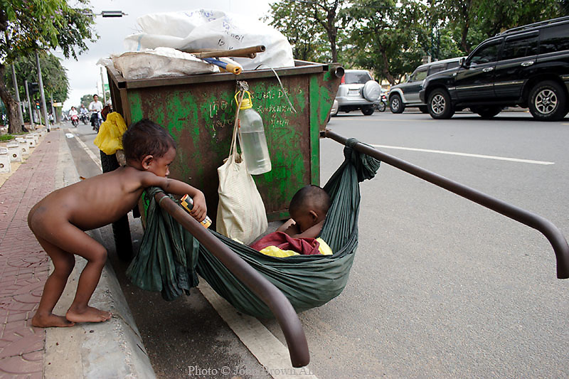 Two young boys whose family sustains themselves by scavenging for recyclable material for the Cintri Garbage Company tend to their refuse collection cart on Norodom Boulevard in Phnom Penh, Cambodia. This area of the city is home  to several banks, foreign embassies, government offices, institutions, foundations and NGO's.
