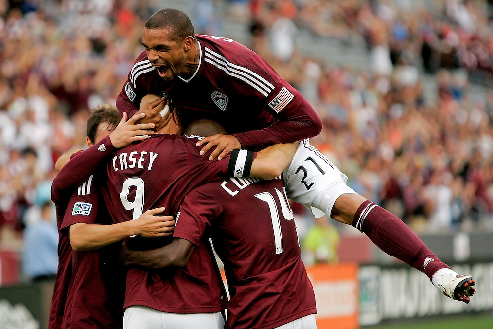 Caleb Folan #21 of the Colorado Rapids leaps onto a group of his teammates as they celebrate a goal by Conor Casey #9 during the first half against the Vancouver Whitecaps at Dick's Sporting Goods Park on July 9, 2011 in Commerce City, Colorado.