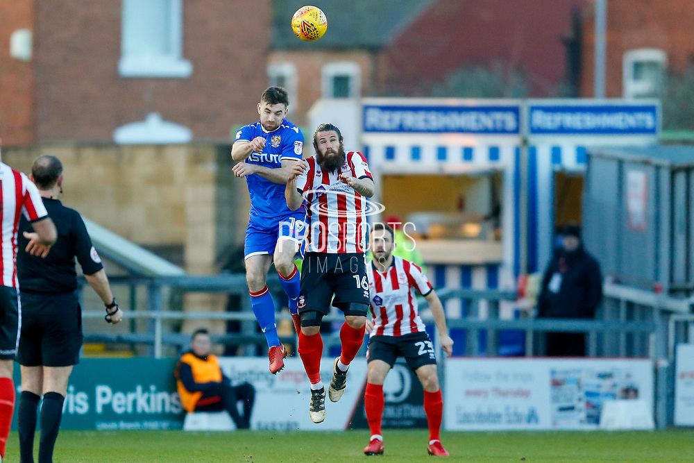 Stevenage forward Danny Newton (19) challenges with Lincoln City midfielder Michael Bostwick (16)  during the EFL Sky Bet League 2 match between Lincoln City and Stevenage at Sincil Bank, Lincoln, United Kingdom on 26 December 2017. Photo by Simon Davies.