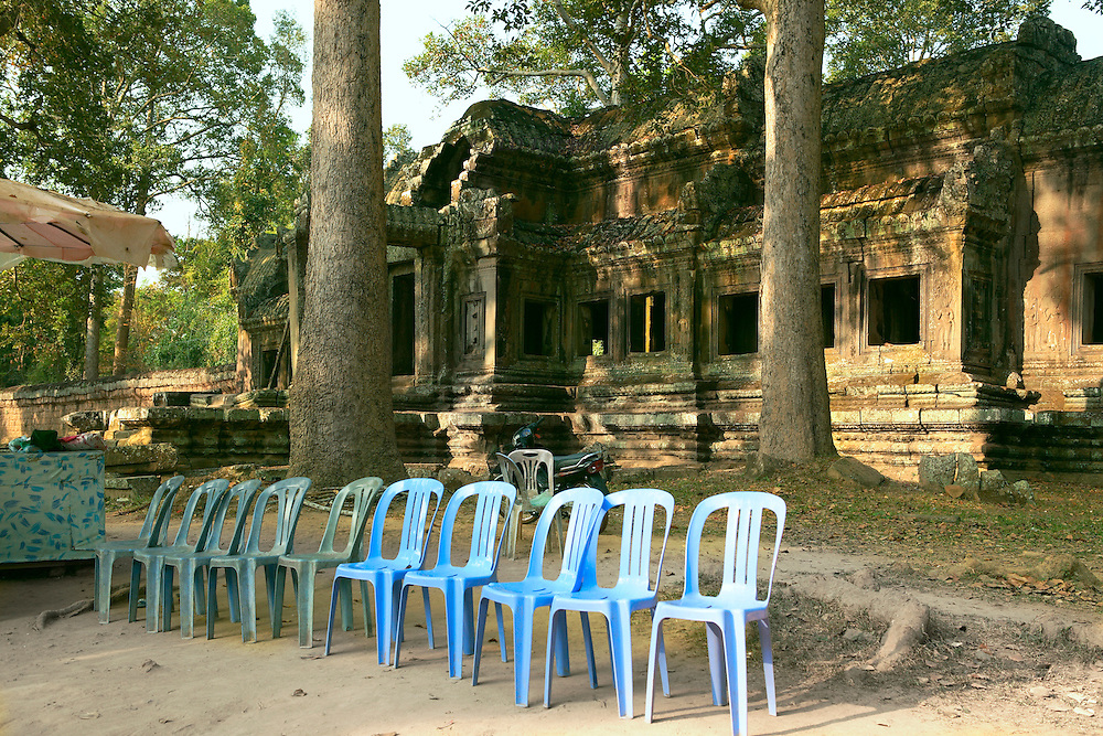 Angkor Thom, row of plastic chairs, waiting for tired tourists to rest and drink water, outside one of the ruined temples ( prasats )