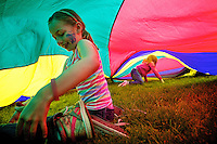 "Sophie Lybarger, 7, plays under a parachute during a game Tuesday of ""sharks and lifeguards"" at McEuen Park. Students from Sorensen Magnet School students spent the day at the park as classwork and events before summer vacation wind down."