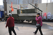 JINAN, CHINA - MARCH 16: (CHINA OUT) <br /> <br /> A Tank Serves For Barbecue<br /> <br /> Two citizens pass by a barbecue vehicle which is modelled on a tank and made by a barbecue owner near Daming Lake on March 16, 2016 in Jinan, Shandong Province of China. The simulated tank is converted from electric truck with a four-meter-long and two-meter-wide iron cover and could accommodate 500 kebabs per time. It still has been installed smoke filter in chimney for environment protection. It\'s said the owner is a tank lover who has worked on barbecue for several years.<br /> ©Exclusivepix Media
