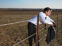 Businessman leaning on fence in the middle of nowhere
