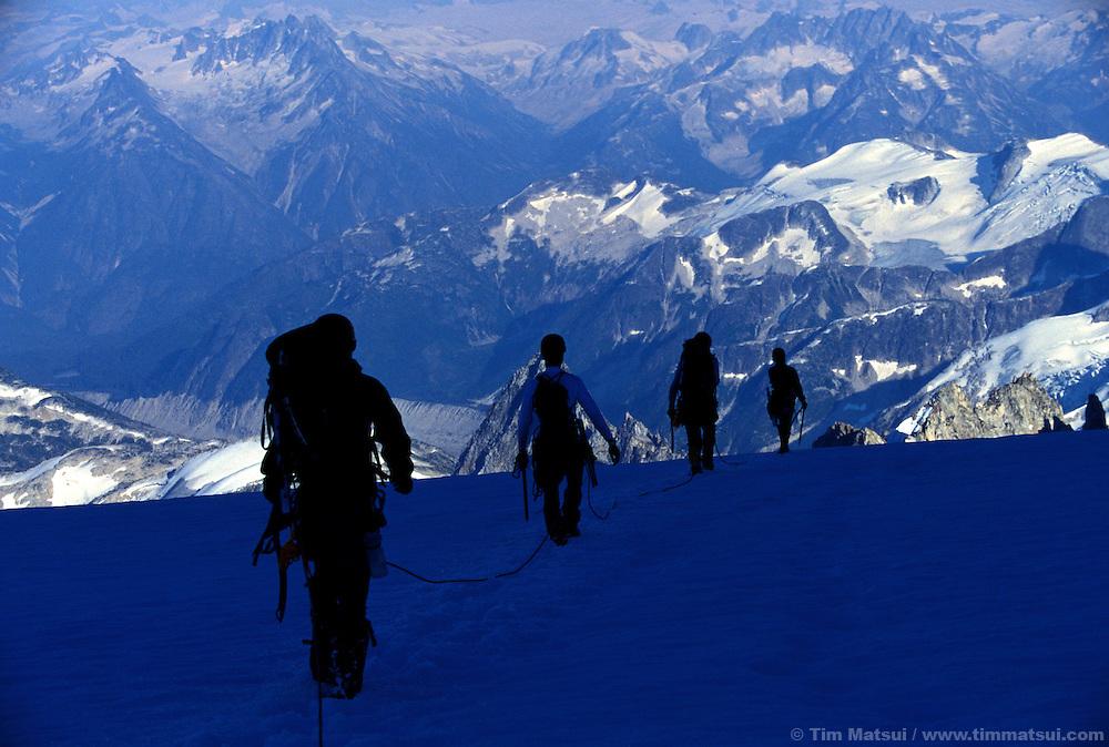 A rope team descends a glacier in British Columbia's Coast Range.
