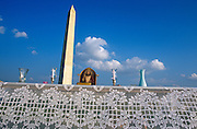 Christian depiction of Jesus and candles on a tabletop beneath the Washington Memorial in Washington DC...The 555 foot (170m) high marble, granite and sandstone Memorial on the National Mall honours George Washington. Completed in 1884, it remains the world's tallest stone structure.
