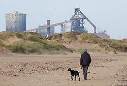 © Licensed to London News Pictures.20/10/15<br /> Redcar, UK. <br /> <br /> A man walks his dog along the beach in front of the recently closed SSI UK steel blast furnace in Redcar, England. The closure of the site marks the end of 170 years of steel making heritage on Teesside and was the first of a number of recent closures of steel making plants across the UK.<br /> <br /> Photo credit : Ian Forsyth/LNP