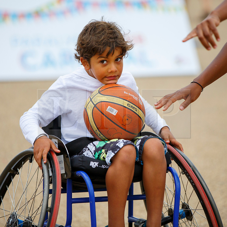 © Licensed to London News Pictures. 03/09/2016. LONDON, UK. Children play paralympics basketball with wheelchairs to experience the disability sports at National Paralympic Day and Liberty Festival in Queen Elizabeth Olympic Park in London on Saturday 3 Spetember 2016. Photo credit : Tolga Akmen/LNP