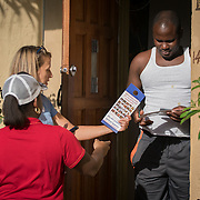 NORTH MIANI, FLORIDA, NOVEMBER 8, 2016<br /> Move On volunteers Francie Peake and  Nelzenna Andrews hand voting percent information to resident Ire Corbett as they knock on doors of homes of voters in the North Miami area as they canvass for democratic votes.<br /> (Photo by Angel Valentin/Freelance)