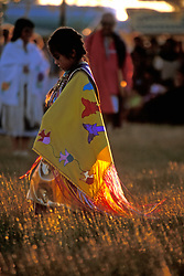 Stock photo of a young Native American girl wrapped in yellow at sunset