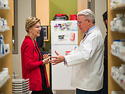 28 DECEMBER 2019 - URBANDALE, IOWA: US Senator ELIZABETH WARREN (D-MA), left, and pharmacist JOHN FORBES, owner of the Medicap Pharmacy in Urbandale, IA, talks about health care policy and consumers' rights at the pharmacy. Warren was at the pharmacy to announce that legislation she wrote will make hearing aids available over the counter. She said it should make hearing aids less expensive and increase competition in the hearing aid industry. The legislation was co-sponsored by Iowa Republican Senator Chuck Grassley and signed into law by President Trump. Warren is campaigning in Iowa this weekend to support her effort to be the Democratic nominee for the US presidential race in 2020. Iowa traditionally hosts the first presidential selection event of the campaign season. The Iowa caucuses are Feb. 3, 2020.        PHOTO BY JACK KURTZ