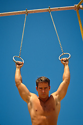 Muscular man on gymnastic rings outdoors