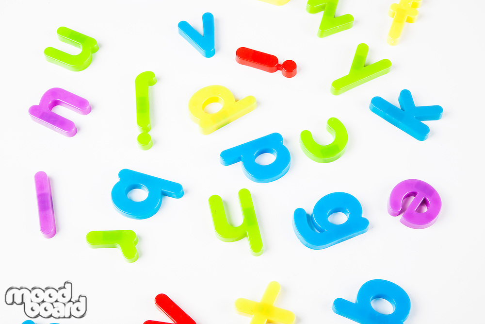 Colorful alphabet magnets scattered over white background