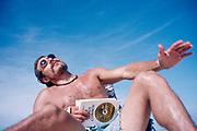 Man reading Edward Abbey's 'The Brave Cowboy' on the beach