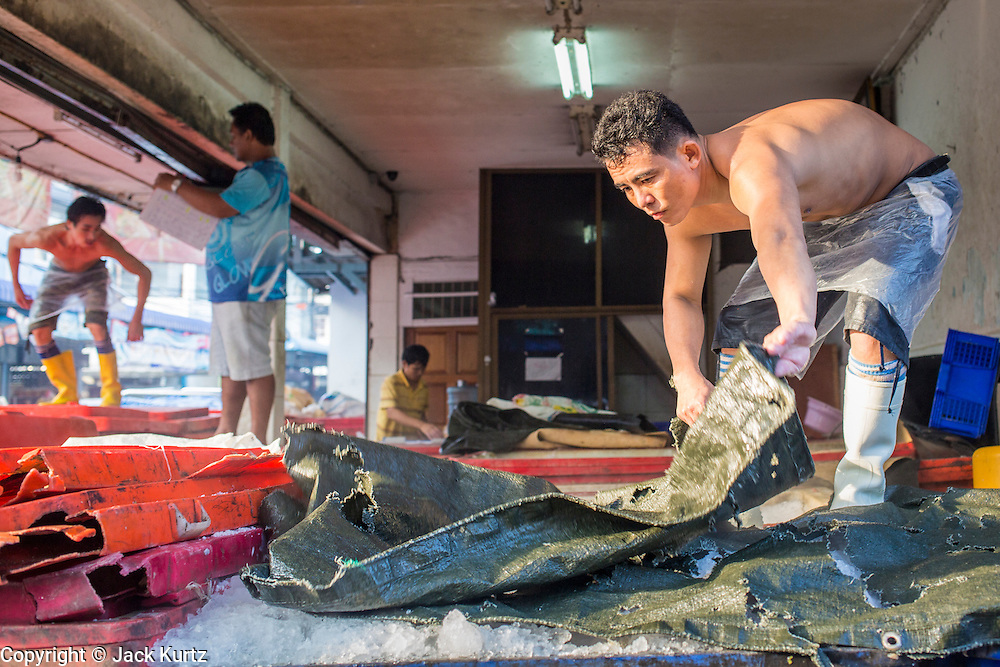 "26 SEPTEMBER 2012 - BANGKOK, THAILAND: Workers pack fresh fish in ice at a wholesale shop in Khlong Toey Market in Bangkok. Khlong Toey (also called Khlong Toei) Market is one of the largest ""wet markets"" in Thailand. The market is located in the midst of one of Bangkok's largest slum areas and close to the city's original deep water port. Thousands of people live in the neighboring slum area. Thousands more shop in the sprawling market for fresh fruits and vegetables as well meat, fish and poultry.   PHOTO BY JACK KURTZ"