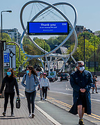 People in masks walk over Wandsworth Bridge in front of an advertising hoarding devoted to messages of support for the NHS and other Care workers on the Wandsworth gyratory. The 'lockdown' continues in London because of the Coronavirus (Covid 19) outbreak.