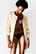 African American model wearing lingerie and gold coat on white background