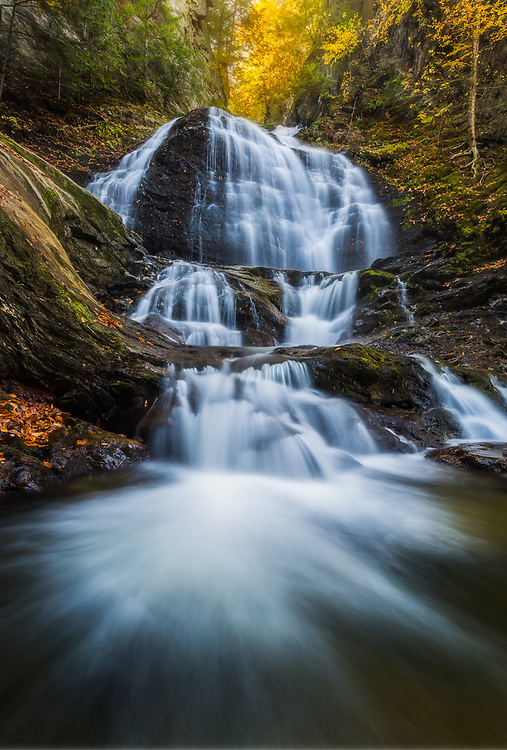 A long exposure and wide angle view combine for an etheral image of autumn foliage at Moss Glen Falls, Stowe, Vermont