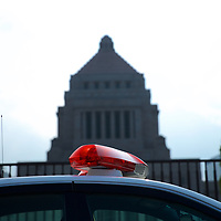 A police car in front of the National Diet building - the center of laws and government in Japan.