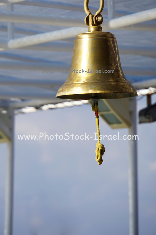 Bronze ship bell against a cloudy sky