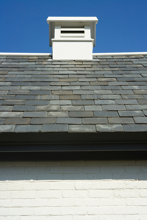 Ridge vent and slate roof on top of a white brick shed on Cape Cod.